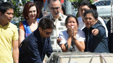 Jessica (C), sister of Filipina overseas worker Joanna Demafelis whose body was found inside a freezer in Kuwait, cries in front of a wooden casket containing her sister's body shortly after its arrival at the international airport in Manila on February 16, 2018, while Philippine Foreign Secretary Alan Peter Cayetano (C-behind w/glasses) looks on. The Philippines on February 12 expanded a ban on its citizens working in Kuwait after President Rodrigo Duterte angrily lashed out at the Gulf state over reports of Filipino workers suffering abuse and exploitation. Authorities say 252,000 Filipinos work in Kuwait, many as maids, yet domestic workers there are not covered by ordinary labour legislation. / AFP PHOTO / TED ALJIBE        (Photo credit should read TED ALJIBE/AFP/Getty Images)