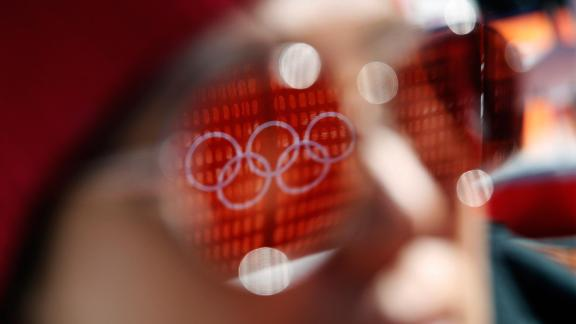 The Olympic rings are reflected in a spectator's sunglasses before the start of the women's super-G.