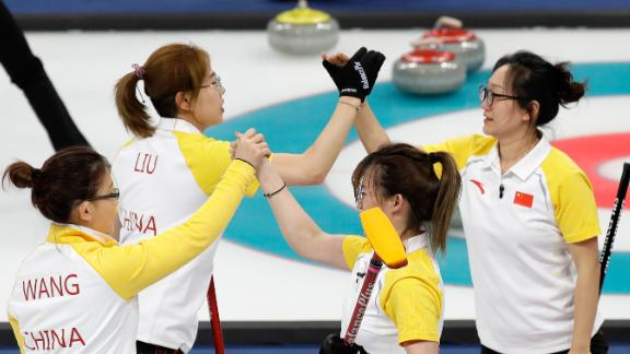 The women's curling team from China celebrates after a win over Japan.