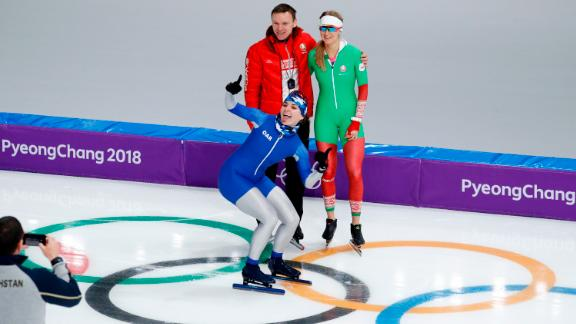 Angelina Golikova, a speedskater from Russia, photobombs teammate Kseniya Sadouskaya and her coach during a practice session.
