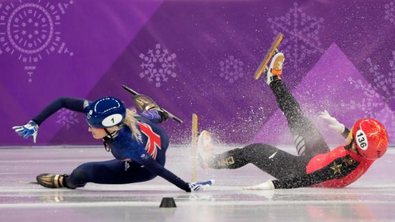 Great Britain's Elise Christie, left, and China's Li Jinyu crash during a short-track semifinal for the 1,500 meters. Christie was taken off the ice on a stretcher.