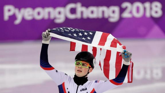 Short-track speedskater John-Henry Krueger celebrates with the American flag after winning silver in the 1,000 meters. Canada's Samuel Girard won the gold.