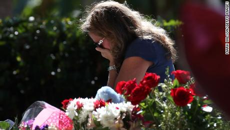 A woman becomes emotional while visiting a temporary memorial at Pine Trails Park on February 17, 2018 in Parkland, Florida. Police have arrested former student Nikolas Cruz and charged him with 17 murders for the shooting at Marjory Stoneman Douglas High School on February 14.