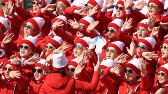 North Korean cheerleaders sing and wave during the men
