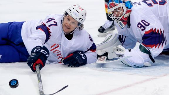 Alexander Bonsaksen and goalie Lars Haugen of Norway reach for the puck during the second period of the preliminary round of their hockey game against Germany.