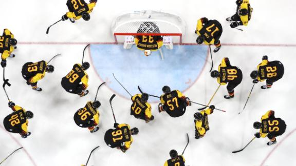 The German team huddles around the net before their game against Norway during the men