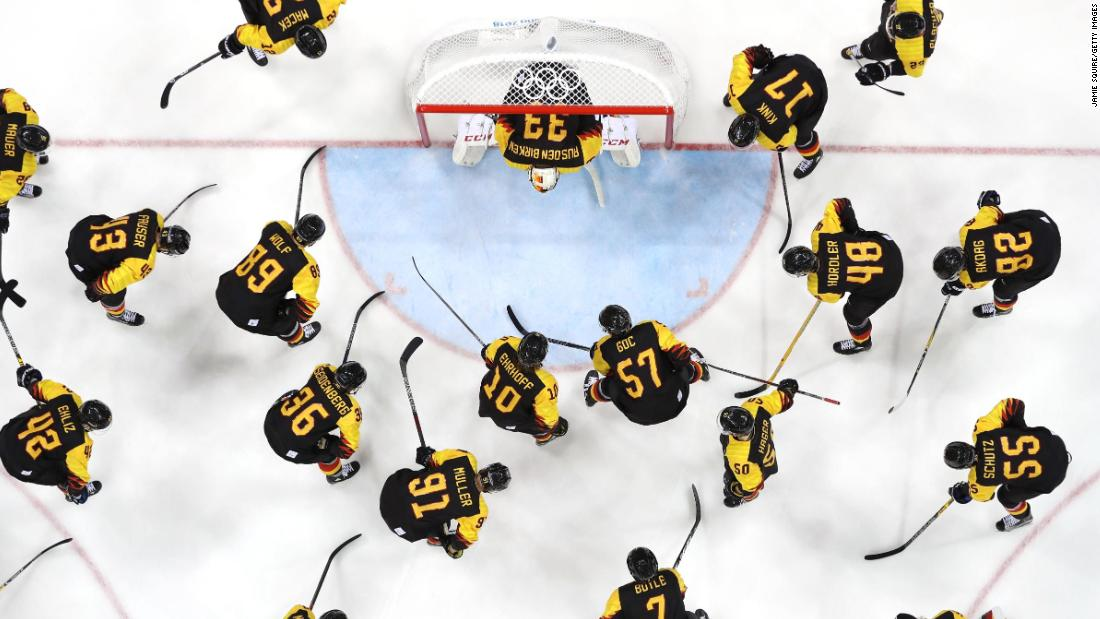 The German team huddles around the net before their game against Norway during the men's ice hockey preliminary round.