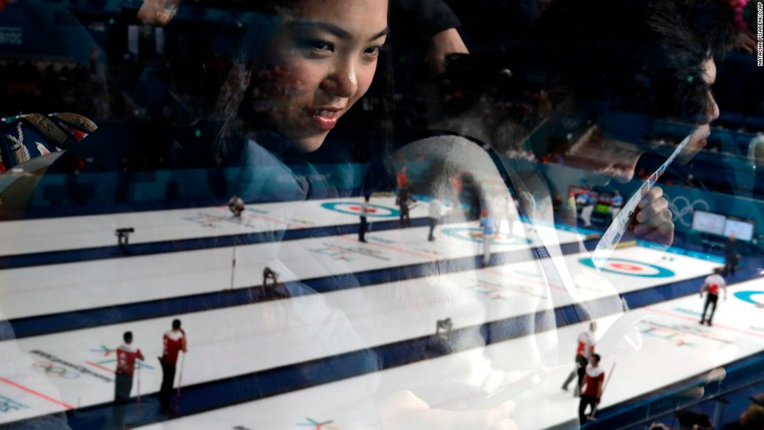 A woman's reflection can be seen as she watches a men's curling match.