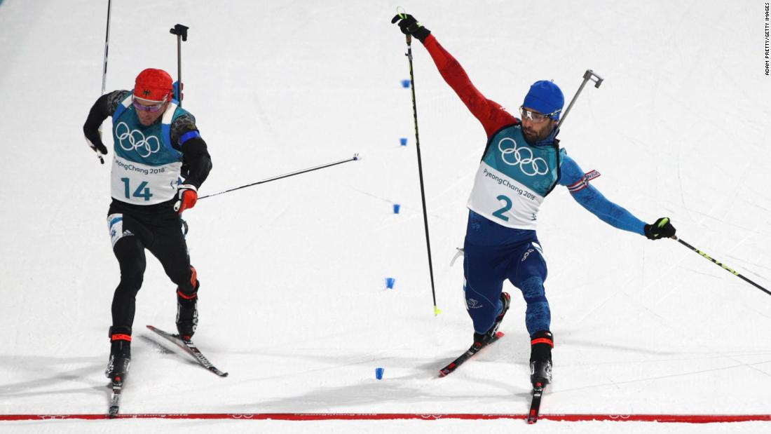 France's Martin Fourcade, right, barely beats Germany's Simon Schempp to the finish line to win gold in the mass-start biathlon.