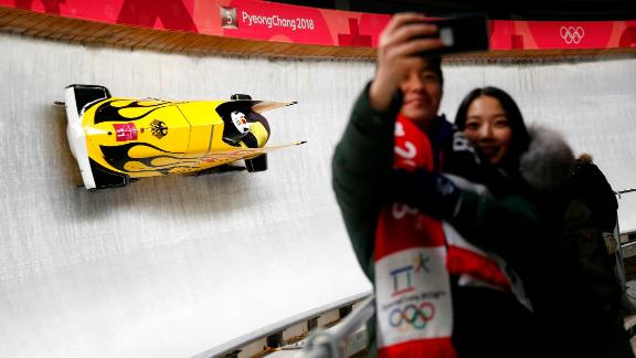 A couple takes a selfie as the German bobsled duo, Nico Walther and Christian Poser, pass by
