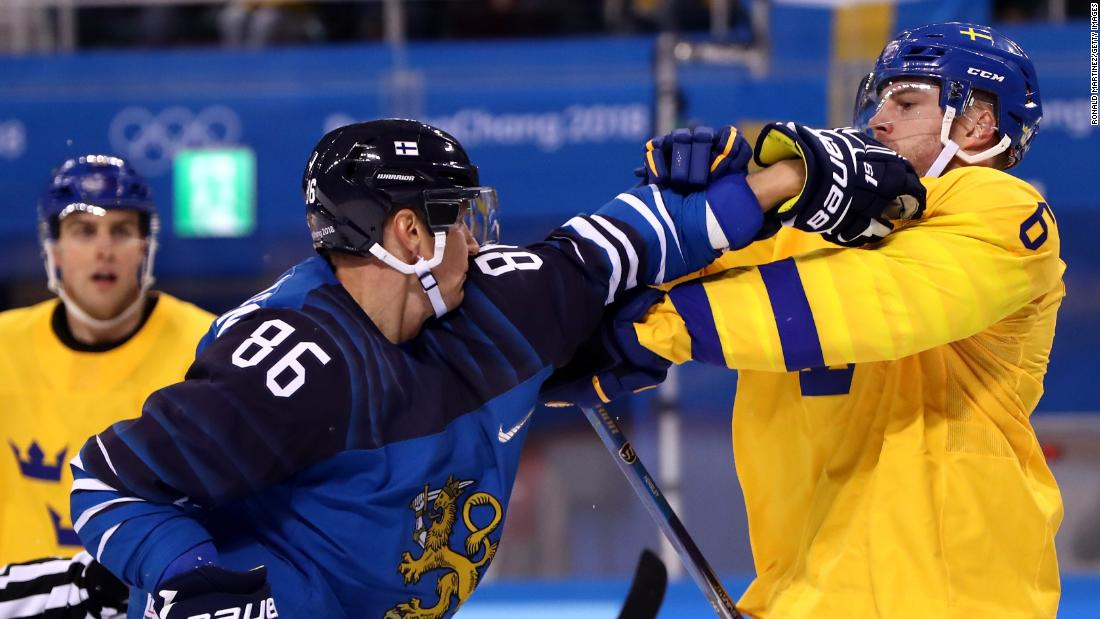 Patrik Hersley, right, of Sweden, and Veli-Matti Savinainen of Finland get tangled up in the first period of their hockey game.