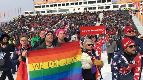Gus Kenworthy's boyfriend Matthew Wilkas holds the rainbow flag as he watches the action.