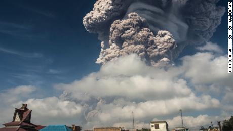 TOPSHOT - Mount Sinabung erupts thick volcanic ash in Karo on Sumatra island on February 19, 2018. An Indonesian volcano erupted February 19, sending a massive column of ash and smoke some 5,000 metres (16,400 feet)into the air, leaving local villages coated in debris and officials scrambling to hand out face masks to residents.  / AFP PHOTO / TIBTA PANGINTIBTA PANGIN/AFP/Getty Images