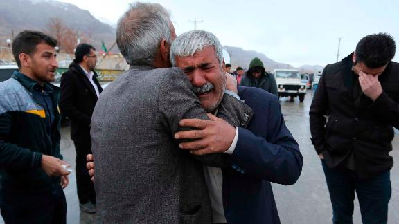 Family members of a plane crash victims weep in the village of Bideh, at the area that the plane crashed, southern Iran, Sunday, Feb. 18, 2018.