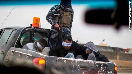 Christian militia fighters from the Nineveh Plain Protection Units (NPU) drive a pick-up truck in Qaraqosh (also known as Hamdaniya), transporting four men, allegedly members of the Islamic State (IS) group that were found inside a tunnel in Mosul.