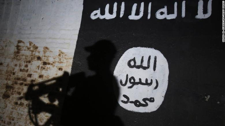 A member of the Iraqi forces walks past a mural bearing the ISIS logo last year.