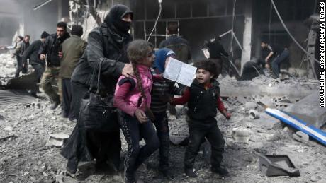 A Syrian woman and children run for cover amid the rubble of buildings following government bombing in the rebel-held town of Hamouria, in the besieged Eastern Ghouta region on the outskirts of the capital Damascus, on February 19, 2018. Heavy Syrian bombardment killed 44 civilians in rebel-held Eastern Ghouta, as regime forces appeared to prepare for an imminent ground assault. / AFP PHOTO / ABDULMONAM EASSA        (Photo credit should read ABDULMONAM EASSA/AFP/Getty Images)