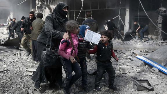 A Syrian woman and children run for cover in Hamouria, in the Eastern Ghouta region.