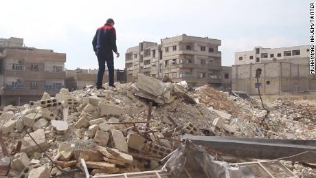 Najem surveys the damage in his neighborhood.