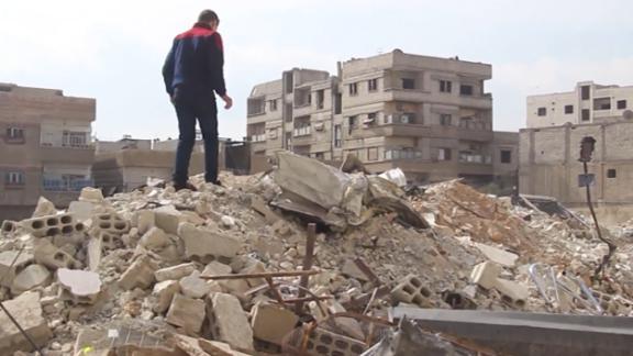 Najem surveys the damage in his neighborhood.