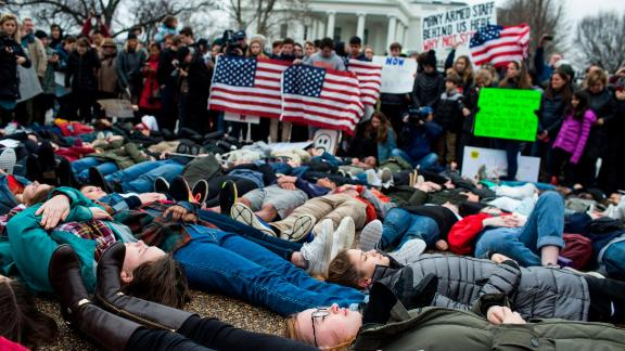 """WASHINGTON, DC - FEBRUARY 19: Demonstrators lie on the ground a """"lie-in"""" demonstration supporting gun control reform near the White House on February 19, 2018 in Washington, DC.  According to a statement from the White House, """"the President is supportive of efforts to improve the Federal background check system."""", in the wake of last weeks shooting at a high school in Parkland, Florida. (Photo by Zach Gibson/Getty Images)"""