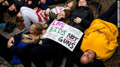 "WASHINGTON, DC - FEBRUARY 19: Demonstrators lie on the ground during a ""lie-in"" demonstration supporting gun control reform near the White House on February 19, 2018 in Washington, DC. According to a statement from the White House, ""the President is supportive of efforts to improve the Federal background check system."", in the wake of last weeks shooting at a high school in Parkland, Florida. (Photo by Zach Gibson/Getty Images)"