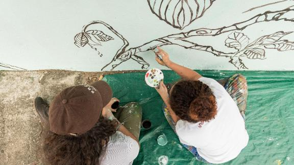 Residents of Punta Santiago, Puerto Rico, outline the foliage for the mural.