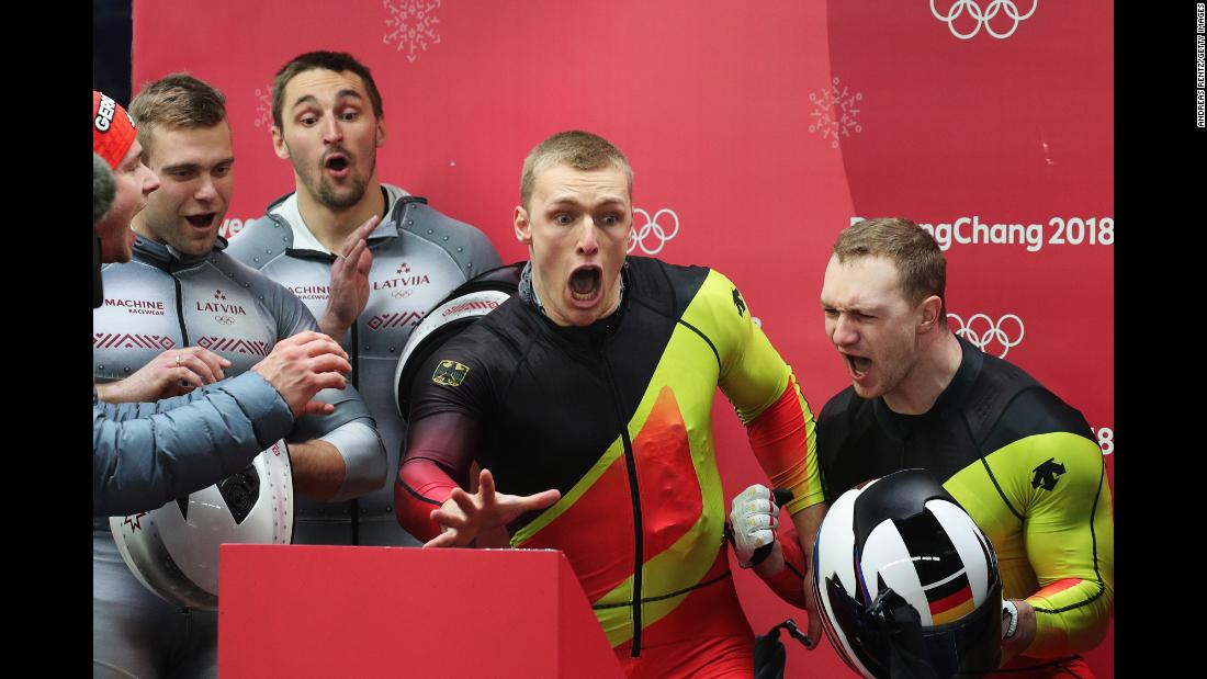 German bobsledders Francesco Friedrich and Thorsten Margis, right, react as they watch the final run by Canada's Justin Kripps and Alexander Kopacz. The two teams will share the gold after finishing with the exact time over four runs.