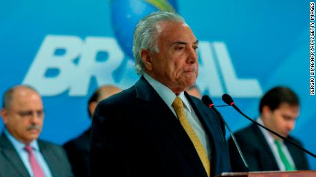Brazilian President Michel Temer gestures during the signature of a decree to send in the army to lead public safety in Rio de Janeiro state, at the Planalto Palace in Brasilia, on February 16, 2018. Army patrols are already used in Rio's favelas ruled by drug gangs, but the decree will now give the military full control of security operations in Rio state, which the president said had virtually been seized by organized crime gangs.  / AFP PHOTO / Sergio LIMA        (Photo credit should read SERGIO LIMA/AFP/Getty Images)