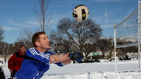 WASHINGTON, DC - JANUARY 25:  Scott Behrens dives for the ball during a friendly game of volleyball with friends in the snow January 25, 2016 in Washington, DC. Winter Storm Jonas hit the East Coast over the weekend, breaking snowfall records, closing places of work, causing 29 storm-related deaths, leaving thousands of homes without power and serious flooding in coastal areas.  (Photo by Win McNamee/Getty Images)