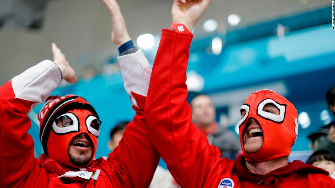 Canadian fans cheer during a men's curling match against Japan.