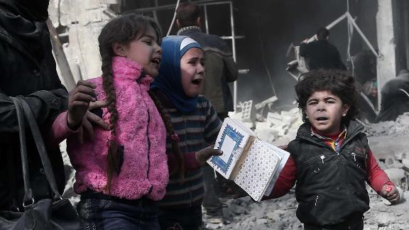 A Syrian woman and children run for cover amid the rubble of buildings following government bombing in the rebel-held town of Hamouria, in the besieged Eastern Ghouta region on the outskirts of the capital Damascus, on February 19, 2018.Heavy Syrian bombardment killed 44 civilians in rebel-held Eastern Ghouta, as regime forces appeared to prepare for an imminent ground assault. / AFP PHOTO / ABDULMONAM EASSA        (Photo credit should read ABDULMONAM EASSA/AFP/Getty Images)