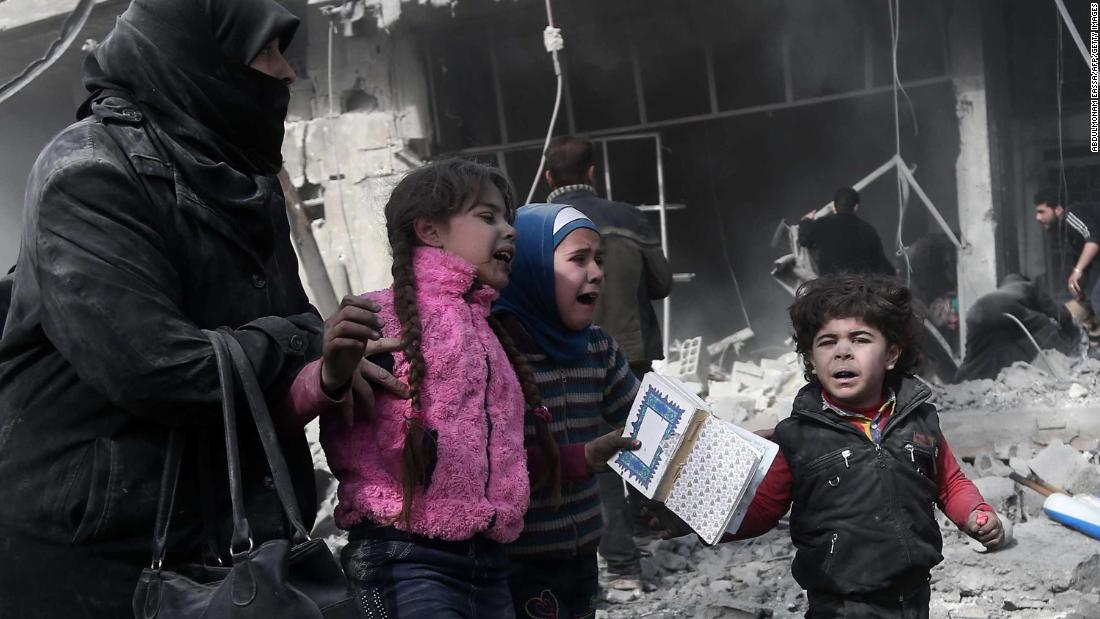 A woman and children run for cover after bombing in the rebel-held town of Hamouria, Syria, on Monday, February 19. More than 100 civilians have been killed in Syria's Eastern Ghouta region in the past 24 hours, according to observers.