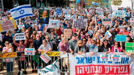 Israeli protesters raise signs as they demonstrate against Prime Minister Benjamin Netanyahu in the wake of police recommendations to indict corruption, in the coastal city of Tel Aviv on February 16, 2018.