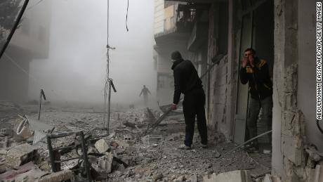 Members of the Syrian civil defence search for injured victims through the rubble of destroyed buildings in an area hit by a reported regime air strike in the rebel-held town of Hamouria, in the besieged Eastern Ghouta region on the outskirts of the capital Damascus, on February 20, 2018. / AFP PHOTO / ABDULMONAM EASSA        (Photo credit should read ABDULMONAM EASSA/AFP/Getty Images)