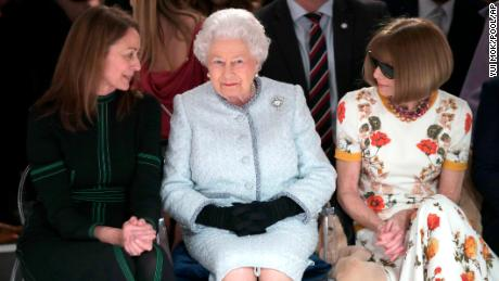 Britain's Queen Elizabeth sits next to fashion editor Anna Wintour, right, and Caroline Rush, chief executive of the British Fashion Council (BFC) as they view Richard Quinn's runway show before presenting him with the inaugural Queen Elizabeth II Award for British Design, as she visits London Fashion Week's BFC Show Space in central London, Tuesday, Feb. 20, 2018. (Yui Mok/Pool photo via AP)