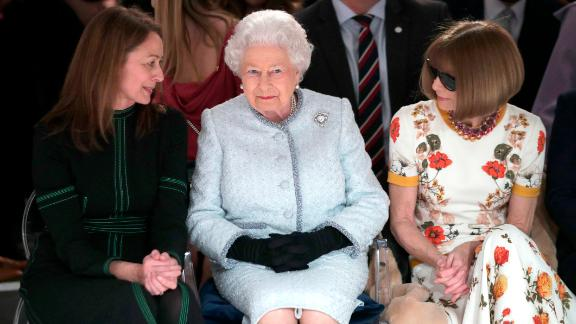 Britain's Queen Elizabeth sits between fashion editor Anna Wintour, right, and Caroline Rush, chief executive of the British Fashion Council (BFC) as they view Richard Quinn's runway show   Tuesday.