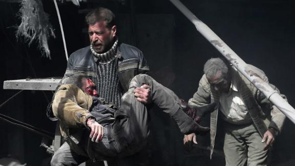 A man carries an injured victim amid the rubble of buildings.