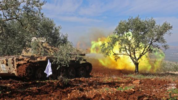 Turkish-backed Syrian rebel fighters fire from the town of Salwah, less than 10 kilometres from the Syria-Turkey border, towards Kurdish forces from the People's Protection Units (YPG) in the Afrin region, on February 19, 2018. Turkey's foreign minister warned against any intervention by Syrian pro-government forces alongside Kurdish militias in northern Syria, saying it would not prevent Ankara from continuing its month-old offensive. / AFP PHOTO / OMAR HAJ KADOUR        (Photo credit should read OMAR HAJ KADOUR/AFP/Getty Images)