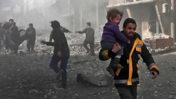 A man carries an infant he rescued from the rubble in Hamouria on February 19.