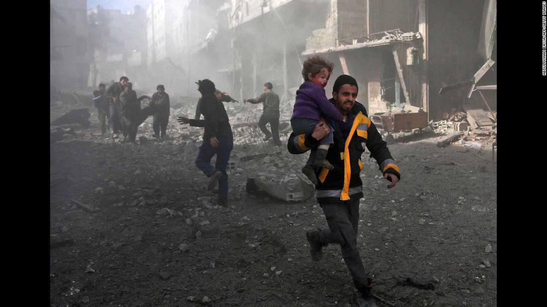 A man carries an infant he rescued from the rubble in Hamouria.