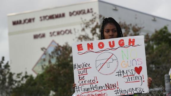 PARKLAND, FL - FEBRUARY 20:  Tyra Heman, a senior at Marjory Stoneman Douglas High School, holds a sign that reads,
