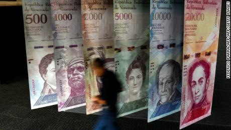 "TOPSHOT - A man walks past banners showing banners depicting Venezuela's currency, the Bolivar, at the Central Bank of Venezuela (BCV) in Caracas on January 31, 2018. Venezuelan President Nicolas Maduro signed the proposal of a new digital currency called ""Petro"" to try to combat the economic crisis. / AFP PHOTO / FEDERICO PARRA        (Photo credit should read FEDERICO PARRA/AFP/Getty Images)"