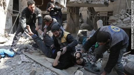 Members of a Syrian civil defence team rescue a man following a reported regime air strike in the rebel-held town of Hamouria, in the besieged Eastern Ghouta region on the outskirts of the capital Damascus on February 21, 2018.  / AFP PHOTO / ABDULMONAM EASSA        (Photo credit should read ABDULMONAM EASSA/AFP/Getty Images)