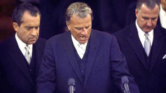 Graham is flanked by US President Richard Nixon, left, and Vice President Spiro Agnew as they bow their heads in prayer in 1969. Graham was speaking at Nixon's inauguration.