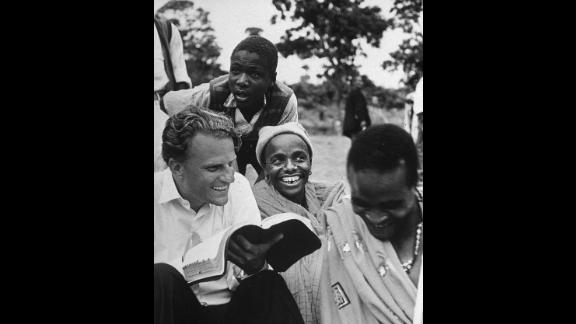 In 1960, Graham explains the Bible to Waarusha warriors in Tanzania.