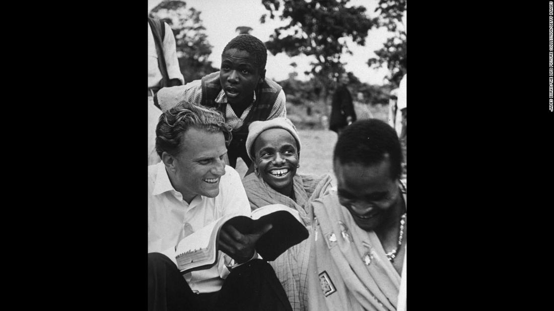 In 1960, Graham explains the Bible to Waarusha warriors in Tanzania.
