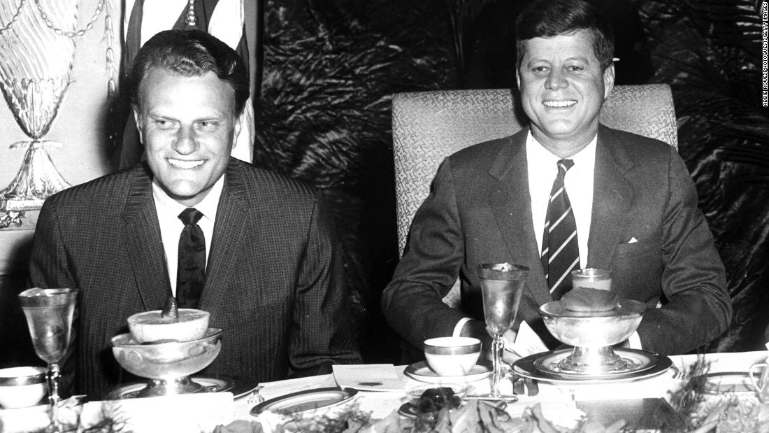 Graham sits with US President John F. Kennedy.