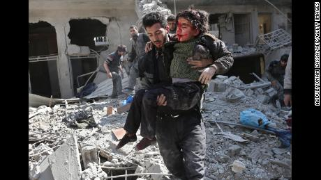 A man rescues a child after a reported regime airstrike in the rebel-held town of Hamouria, Syria, in the besieged Eastern Ghouta region on February 21.