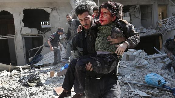 A man rescues a child after a reported regime airstrike in Hamurriya, Eastern Ghouta, on Wednesday.